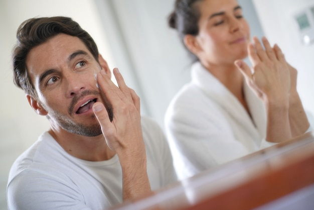 Gorgeous couple going through daily beauty regime in bathroom
