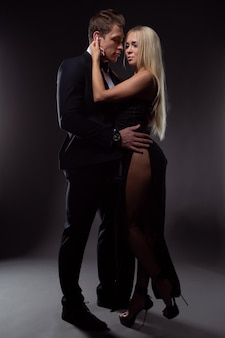 Gorgeous couple in love in elegant evening dresses gently embracing on a dark background