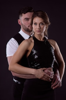 Gorgeous couple in love in stylish evening dresses in a tender embrace