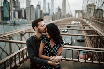 Gorgeous couple of American man with beard and tender Eastern woman hug each other