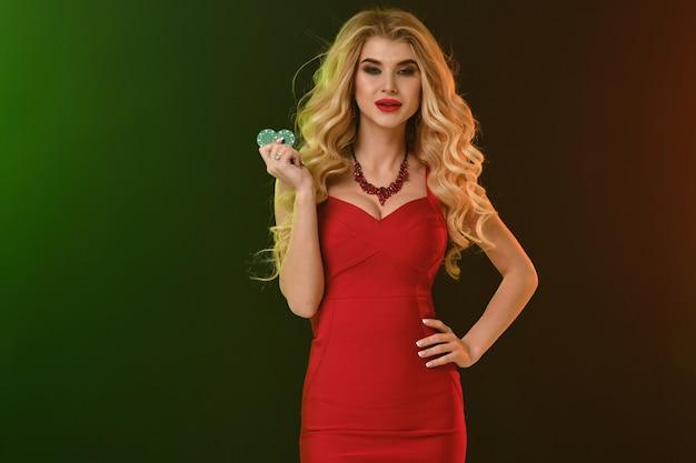 ゴージャスな巻き毛の金髪の女性、明るいメイク、赤いフィッティングドレスとネックレス。彼女は微笑んで、2つの緑色のチップを見せ、腰に手を当て、カラフルな背景でポーズをとります。ポーカー、カジノ。クローズアップ、コピースペース