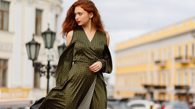 Gorgeous curly ginger woman with red lips posing outdoor in warm spring day.