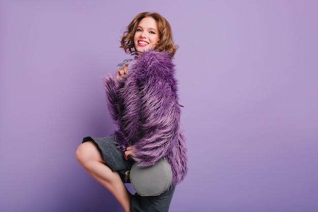明るい壁の前で踊るスタイリッシュな紫色のジャケットのゴージャスな巻き毛の女の子