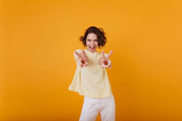성실한 미소로 노란색 티셔츠 재미있는 춤에 화려한 곱슬 소녀. 평온한 갈색 머리 여자가 오싹하고 웃고.