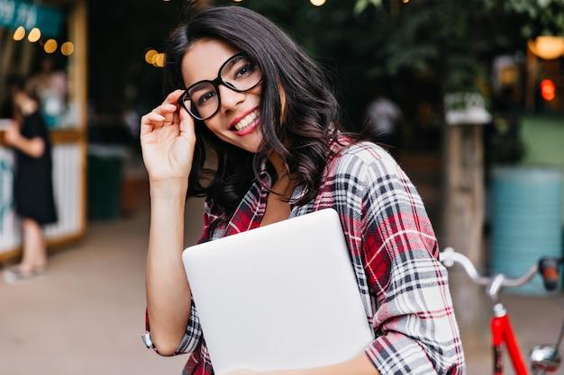 ノートパソコンを持って通りに立っているゴージャスな巻き毛の女の子。市松模様のシャツを着たスマートな女子学生の屋外写真。