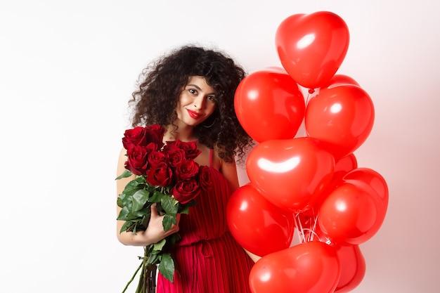 이브닝 드레스에 화려한 곱슬 머리 여자 친구, 데이트, 남자 친구에서 빨간 장미를 들고 로맨틱 하트 풍선, 흰색 배경 근처 포즈.