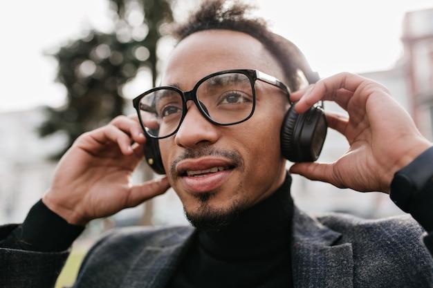 그의 헤드폰을 만지고 화려한 어두운 눈동자 혼혈 남자. 아침에 정장 듣는 음악에 자신감 갈색 머리 아프리카 남자의 클로즈업 초상화.