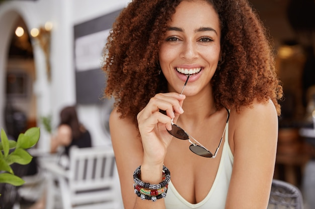 Gorgeous dark skinned woman with pleased expression, holds sunglasses, has curly bushy hair, sits against cafe interior.