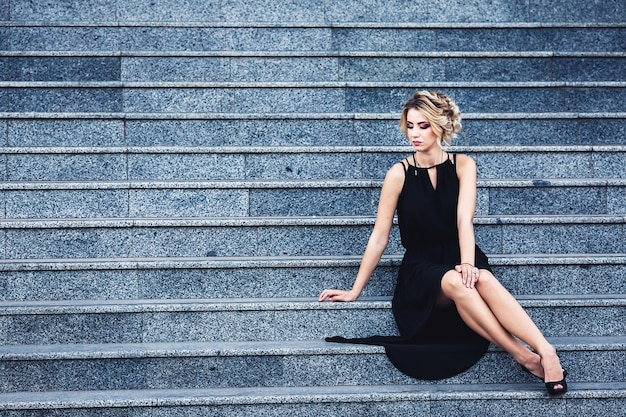 Gorgeous elegant woman in a black dress sits on the steps and waits thoughtfully.