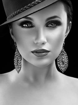 스튜디오에서 포즈 모자에 화려한 우아한 여자