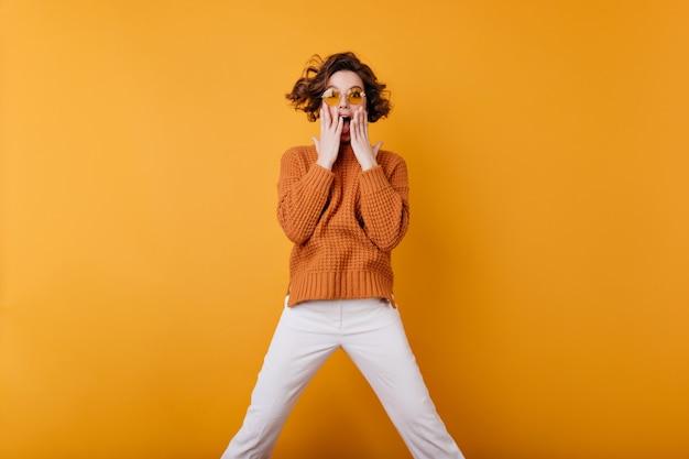 驚きを表現するトレンディな黄色のサングラスでゴージャスな感情的な女性。茶色の髪の少女の屋内の肖像画は、白いズボンと居心地の良いセーターを着ています。