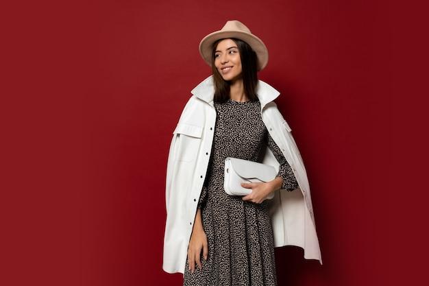 Великолепная европейская брюнетка в модном белом пиджаке и платье с принтом позирует. держит кожаную сумочку.