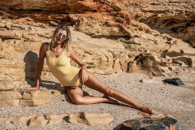 岩の多いビーチでポーズをとるゴージャスなファッションモデル。