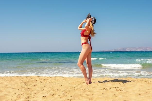 Великолепная фотомодель позирует на песчаном пляже.