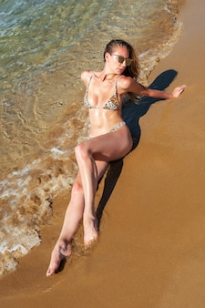 Gorgeous fashion model posing on a sand beach