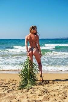 Gorgeous fashion model with palm leaf posing on a sand beach