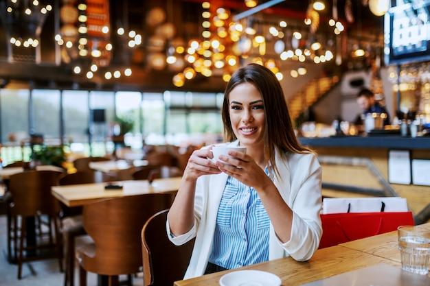 Шикарная модная кавказская брюнетка с красивой улыбкой сидит в кафе