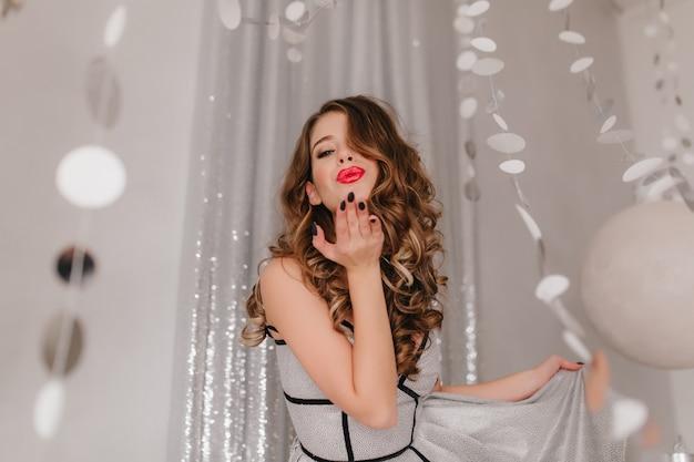 Шикарная, модная кудрявая темноволосая девушка шлет воздушный поцелуй. женщина позирует на стене серебряных блестящих гирлянд