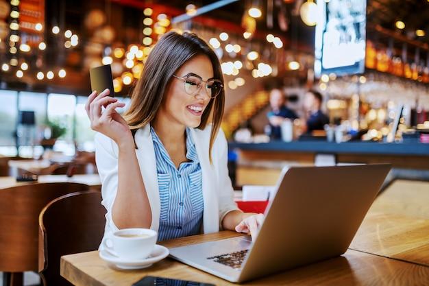 Шикарная модная улыбающаяся кавказская брюнетка сидит в кафе