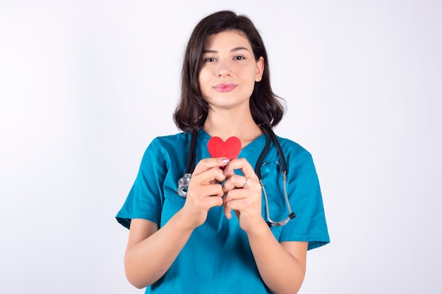 Великолепная женщина-врач, используя красное сердце на пустое пространство