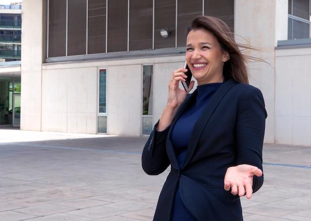 친근한 대화에서 전화로 이야기하고 웃고 화려한 여성 임원