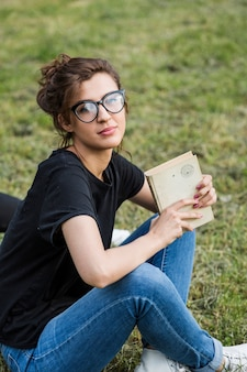 Gorgeous female holding book sitting on grass