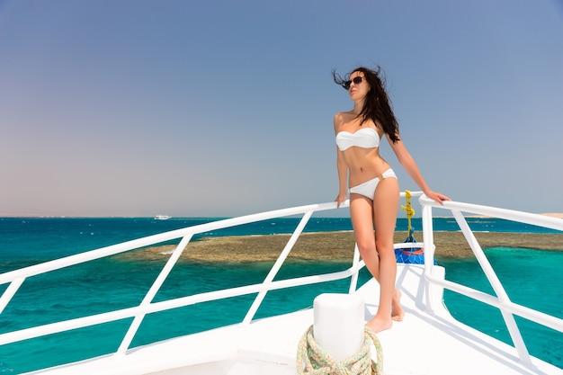 晴れた夏の日にヨットの鼻の上に立っている白い水着のゴージャスな女性、そよ風の発達する髪、背景の美しいターコイズブルーの海