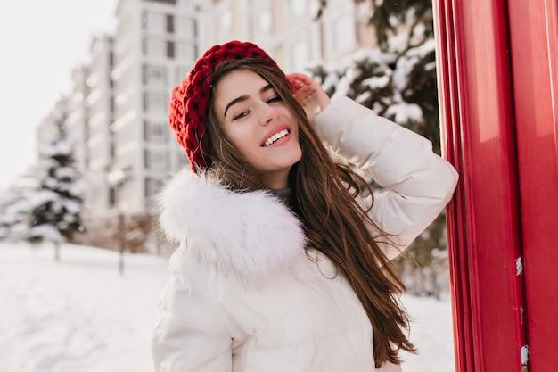良い気分で雪に覆われた通りでポーズをとってストレートの髪型を持つ豪華な女性モデル。冬の間に楽しんでいるニットの赤い帽子のうれしい淡い女性の屋外の写真