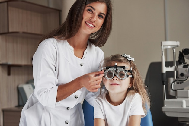 Gorgeous female ophthalmologist smiling when doing her job in cabinet with little girl.