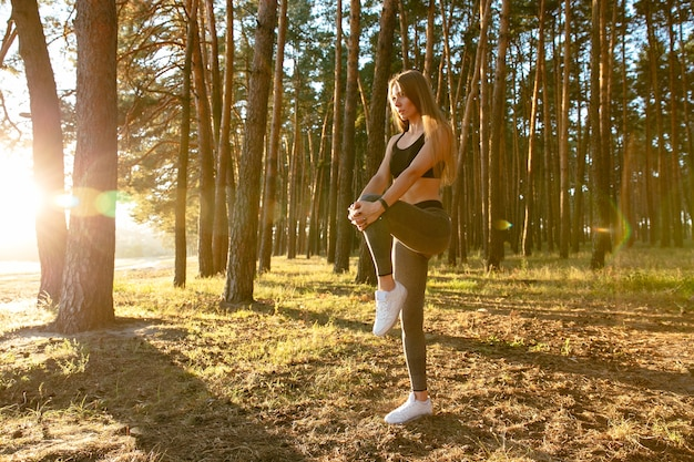 Gorgeous female runner doing stretching exercise, workout in the wood in the sun