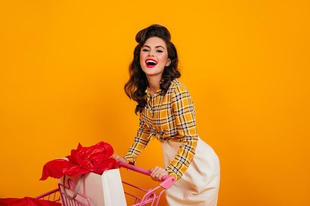 カメラで笑っているゴージャスな女性の買い物中毒者。黄色の背景に幸せを表現するピンナップガール。