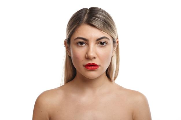 Splendida donna con capelli biondi e labbra rosse in posa nuda, in piedi vicino al marito barbuto prima di andare a letto. concetto di persone, relazioni, sesso, sessualità, passione e sensualità