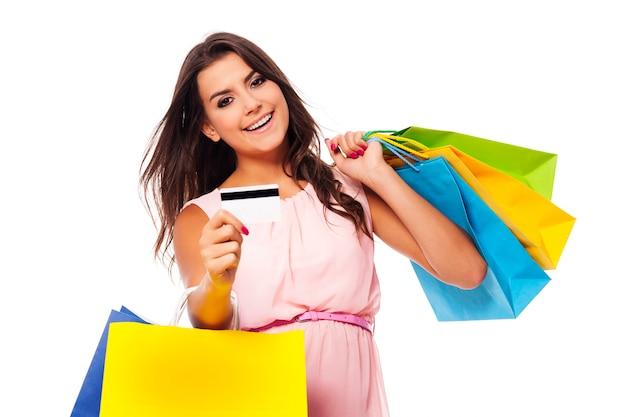 Splendida donna con borsa della spesa multicolore e carta di credito