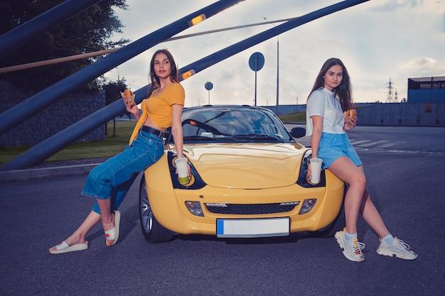 캐주얼 한 옷을 입은 화려한 여성들이 노란색 자동차 카브리올레의 두건에 앉아있는 동안 종이컵에 햄버거와 음료를 들고 있습니다.