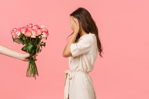 Gorgeous feminine caucasian woman in fancy dress, close eyes with palms as waiting surprise, hand holding lovely bouquet roses, secret admirer express affection with gift, pink