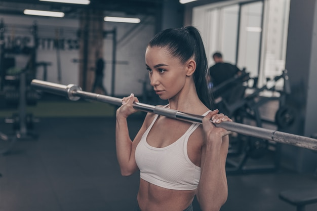 Gorgeous fit and toned sportswoman lifting barbell at the gym, copy space on the side
