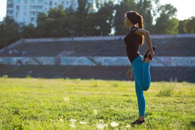 スタジアムでのトレーニングの前にストレッチするゴージャスなフィットネス女性。太陽光線による屋外撮影。テキスト用のスペース