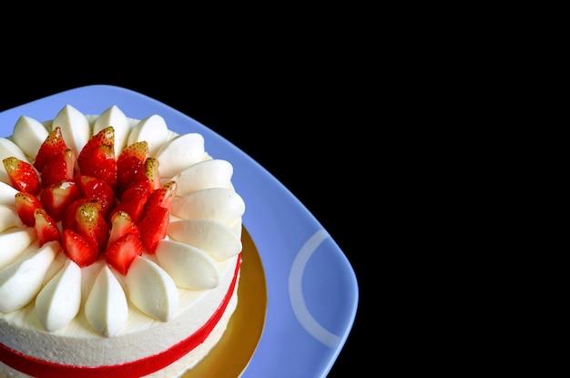 Gorgeous fresh strawberry vanilla short cake on black background with copy space