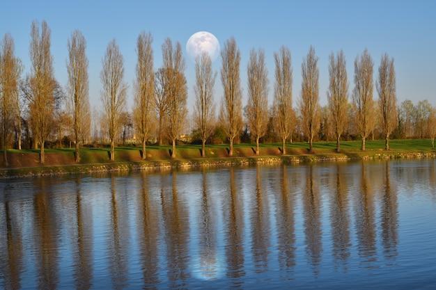 Великолепная полная луна в сельской местности отражается в реке