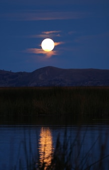 Gorgeous full moon view from uros floating islands on lake titicaca, puno, peru, south america