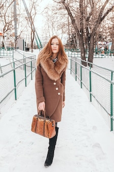 Gorgeous ginger woman in winter park