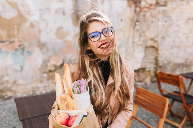 Gorgeous girl after photosession bought fresh food and drinks coffee enjoying a sunny day. stylish young female photographer holding grocery bag and cup of cappuccino posing in the outdoor cafe.