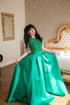Шикарная девушка в изумрудном платье в дорогом интерьере готовится к вечеринке