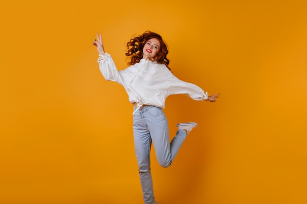 ジャンプするブルージーンズのゴージャスな女の子。オレンジ色の壁で踊る夢のような生姜の女性の屋内写真。