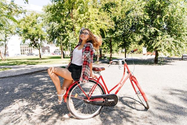 公園で夏を楽しんでいる市松模様のシャツを着たゴージャスな女の子。赤い自転車に座って笑っているかわいい女性モデルの屋外写真。