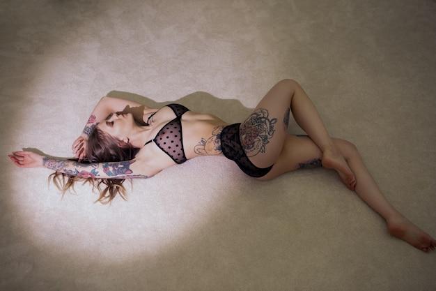 Великолепная девушка лежит на полу в кружевном нижнем белье