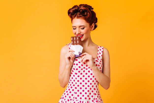 초콜릿을 먹는 폴카 도트 드레스에 화려한 소녀. 노란색 공간에 디저트를 즐기는 생강 핀업 레이디의 스튜디오 샷.