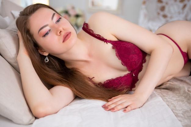 Великолепная девушка в красном кружевном нижнем белье лежит в своей постели