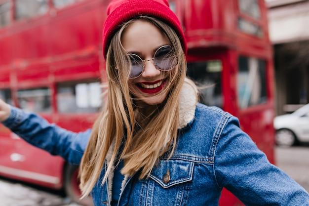 トレンディな帽子をかぶったゴージャスな女の子が通りを騙しながら笑っています。デニムジャケットで楽しいブロンドの女性の屋外ショット