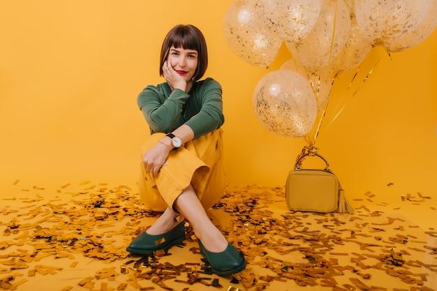 足を組んで座っている腕時計のゴージャスな女の子。彼女の誕生日にリラックスしているファッショナブルな女性の屋内写真。